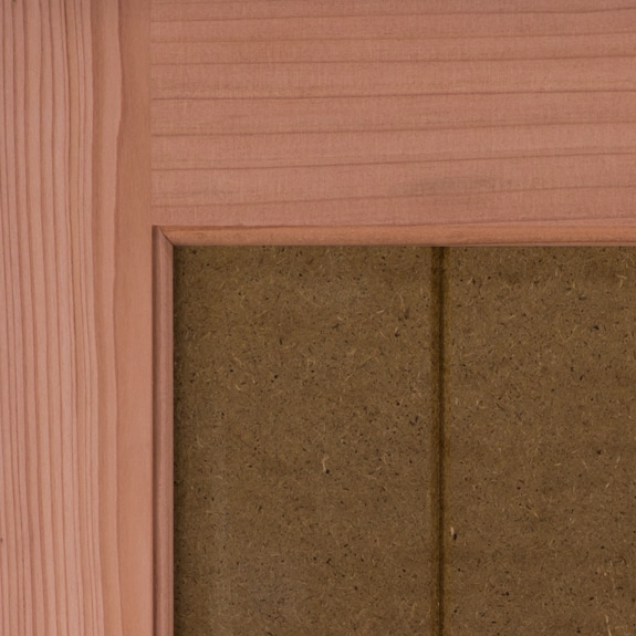 Outdoor wood shutters in California redwood with solid grooved panels.
