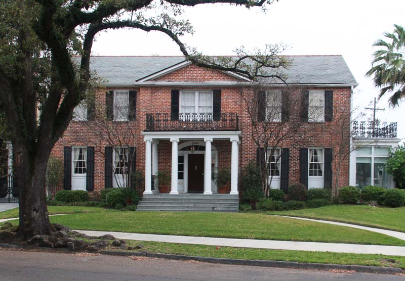 Southern New Orleans brick house with black exterior shutters.