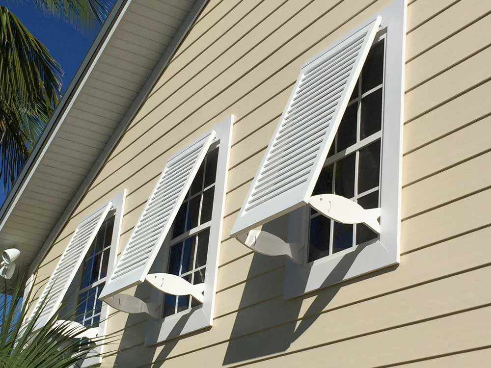 Fixed tropical exterior bahama shutters with cutout fish supports in Florida.