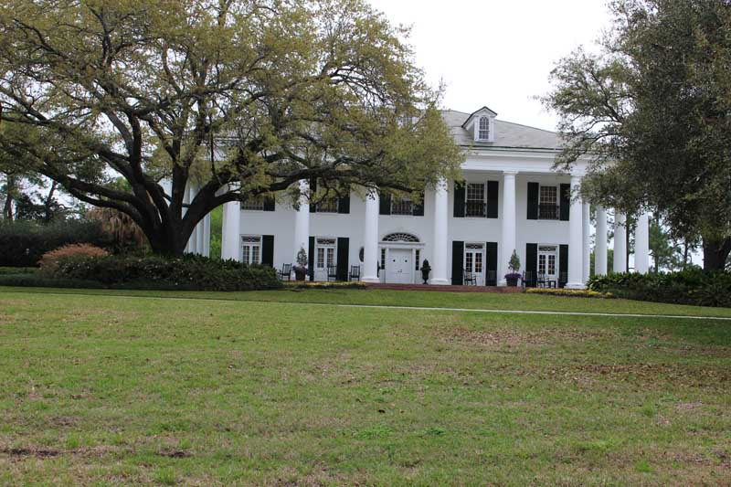 White plantation home with black shutters.