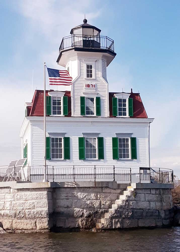Green exterior weather-resistant shutters installed on a lighthouse in the Hudson River.