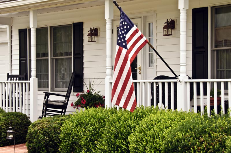 Black exterior shutters on the porch with an American flag.