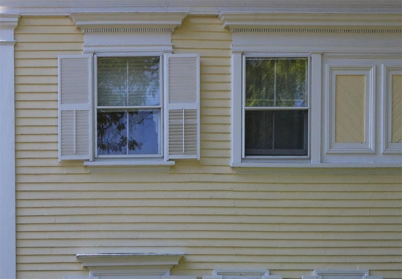 Exterior shutter tails on a yellow house.