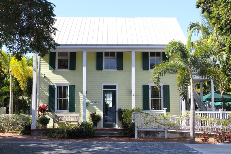 Green exterior shutters installed on a yellow tropical house in Florida.