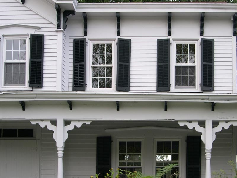 Historic wood farmhouse louvered panels installed on a white house.