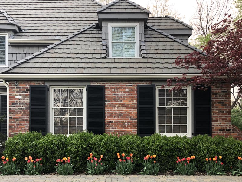 Black exterior wood shutters installed on a brick house.