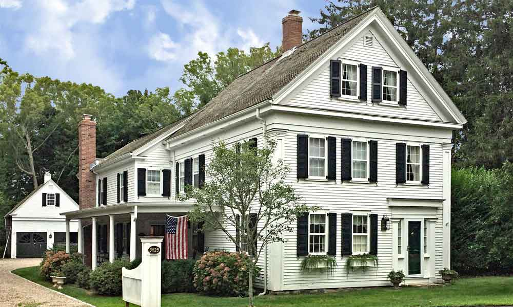 Historic house with black exterior shutters and functional hardware.