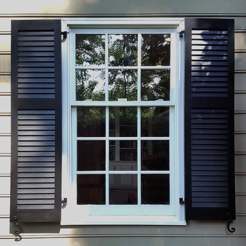 Louvered black shutters installed on exterior windows.