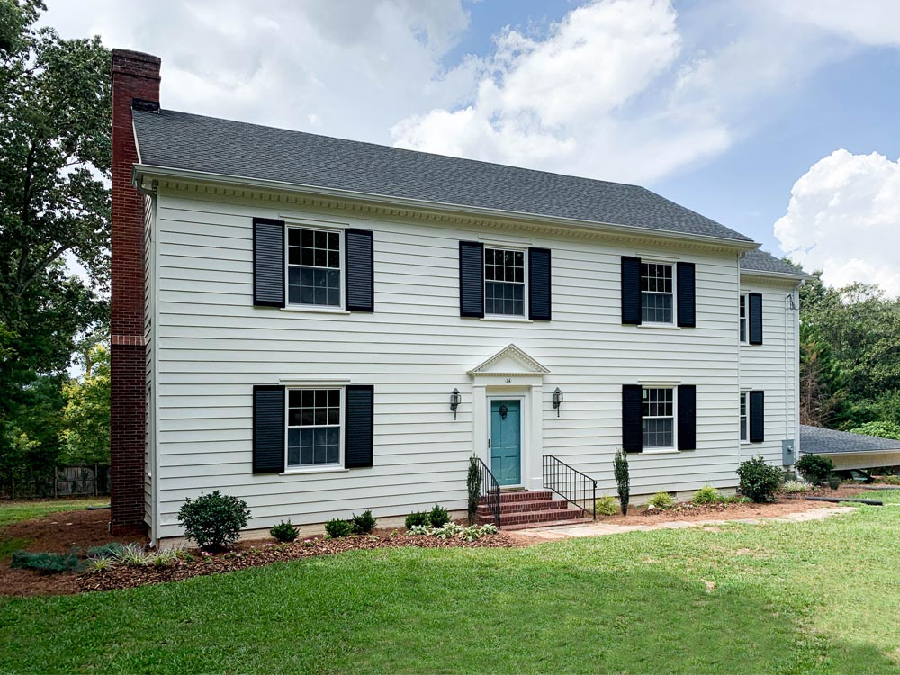 Black louvered shutters installed on a colonial white house.