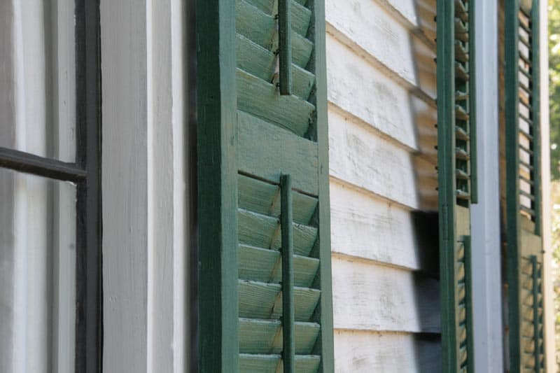 Exterior green shutters on a white house.