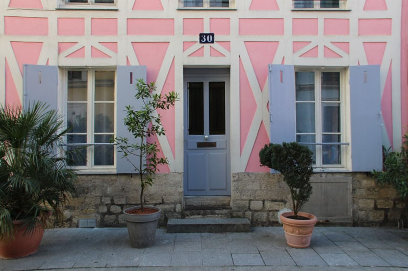 Colorful outdoor French shutters on pink home in Paris.