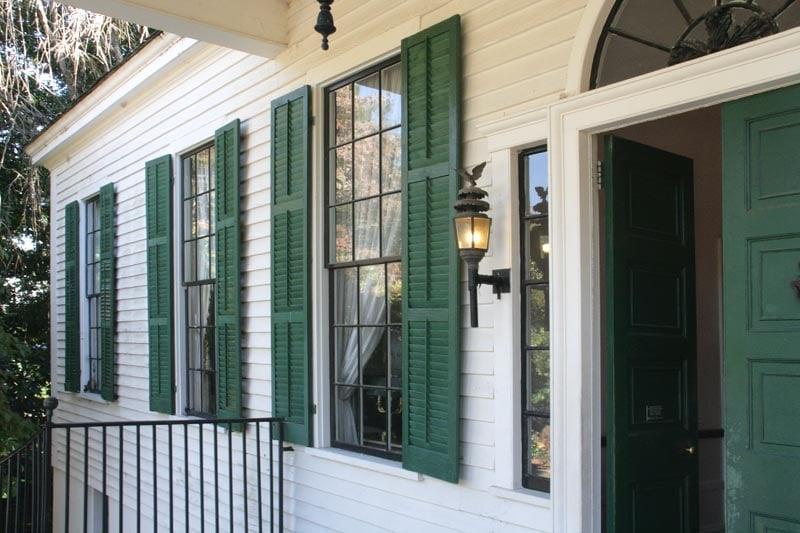 Historical exterior plantation green shutters on a white house.
