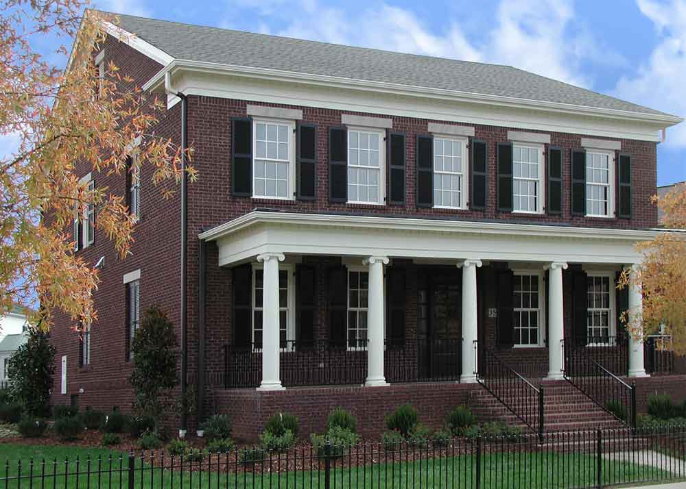 Brick house with outdoor black louvered shutters installed.