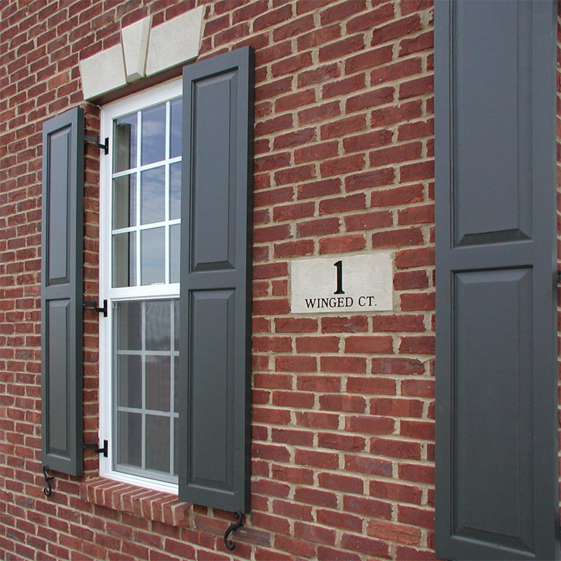 Raised panel exterior shutters installed on brick.
