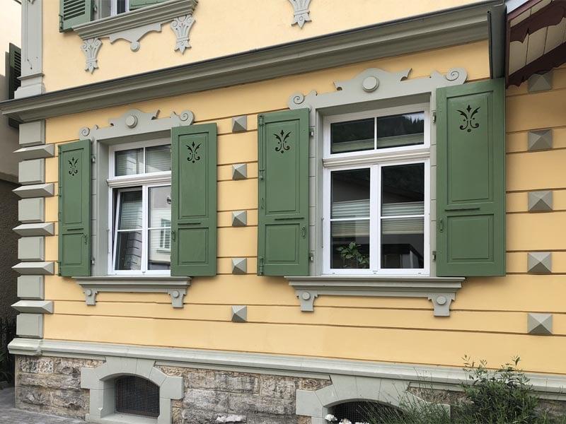 Raised panel shutters with fleur de lis cutouts in Switzerland.