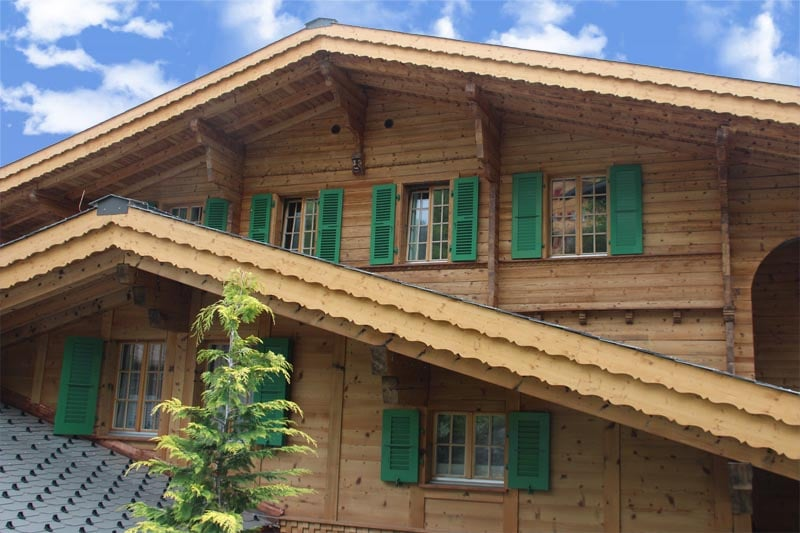 Closeup of Swiss Alpine home with green shutters