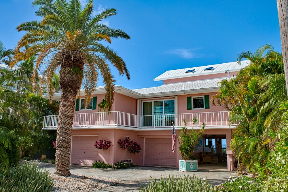 Pink Florida house with wood exterior shutters.