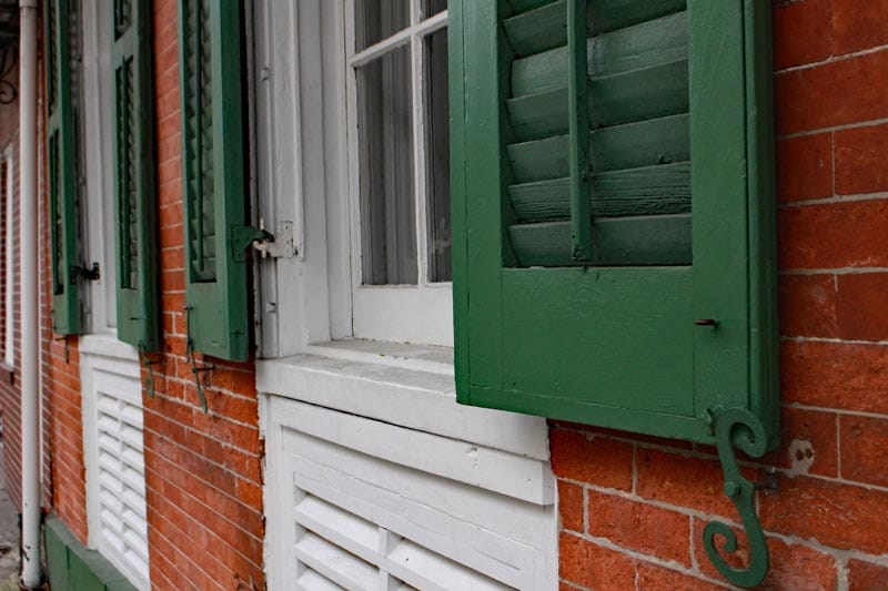 Exterior green shutters with movable louvers in New Orleans.