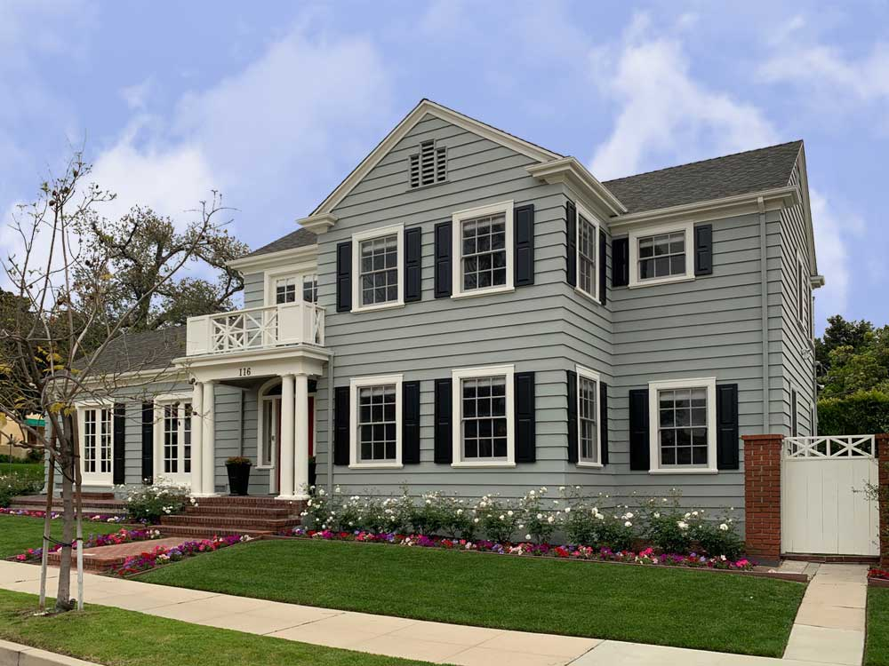 Gray house with black raised panel exterior shutters.